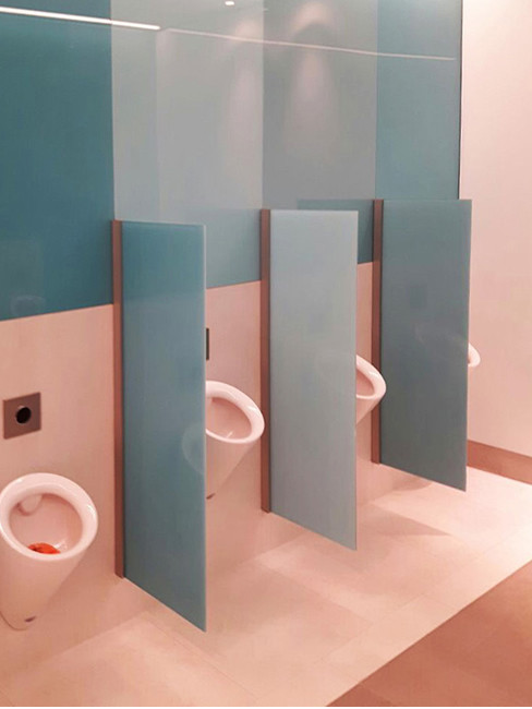 Urinals by Starck with pubic walls made of satin glass.